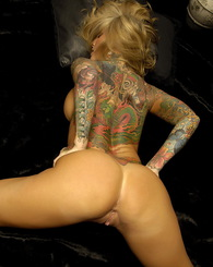 The gorgeous Janine on a leather couch by the fireplace teasing her sexy body and tattooed body